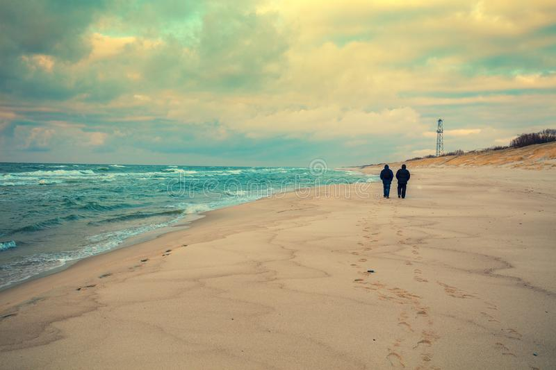 Two men walking on the beach in winter royalty free stock photos