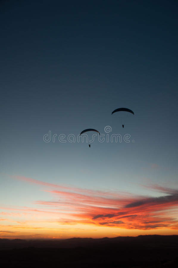 Silhouette of two paraglider at sunset. royalty free stock photos