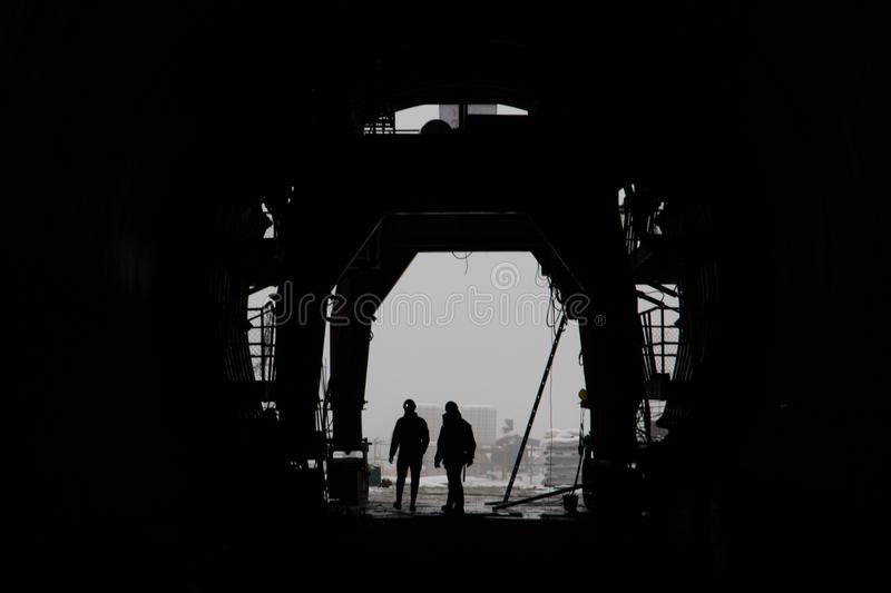 The silhouette of two people in a high-speed railway tunnel under construction royalty free stock photography