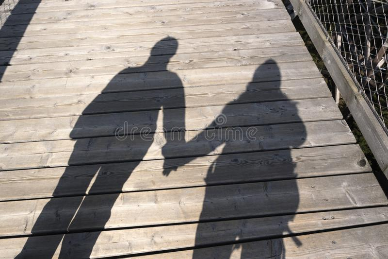 Silhouette of two people holding their hands. In sunlight, a couple of hikers walking a wood path stock photo