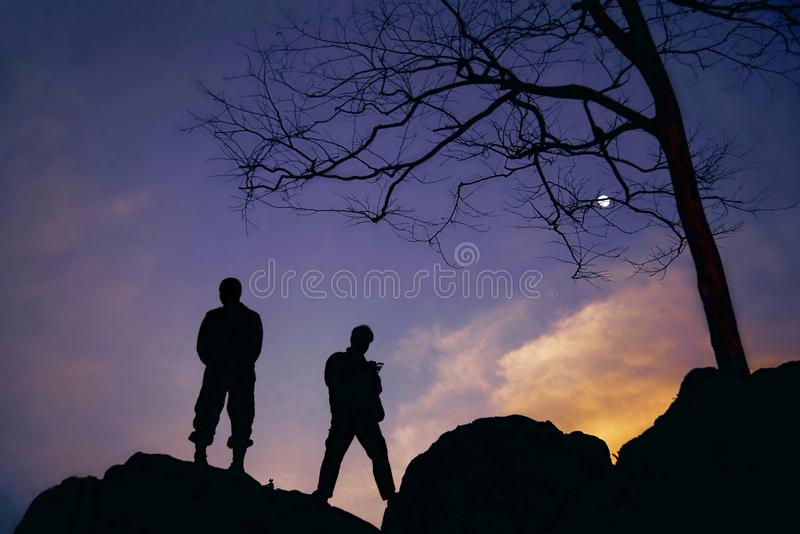 Silhouette of two soldiers on the top mountain at twilight stock images