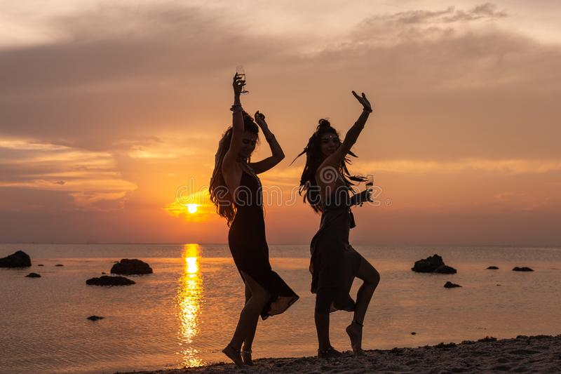 Silhouette of two young beautiful girls having fun on the beach at sunset royalty free stock photos