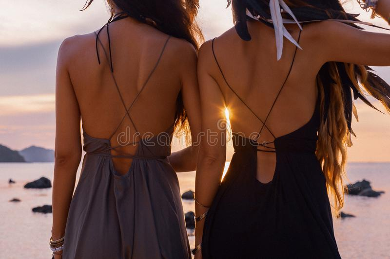 Silhouette of two young beautiful girls having fun on the beach at sunset royalty free stock photo