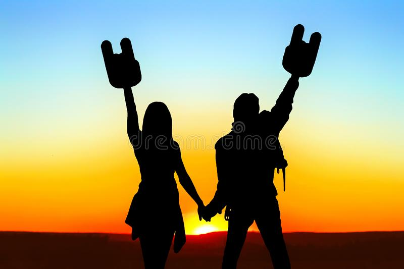 Silhouette of a guy with a girl at sunset. Silhouette of two young men boy and girl holding hands at sunset, hands up with horns stock image