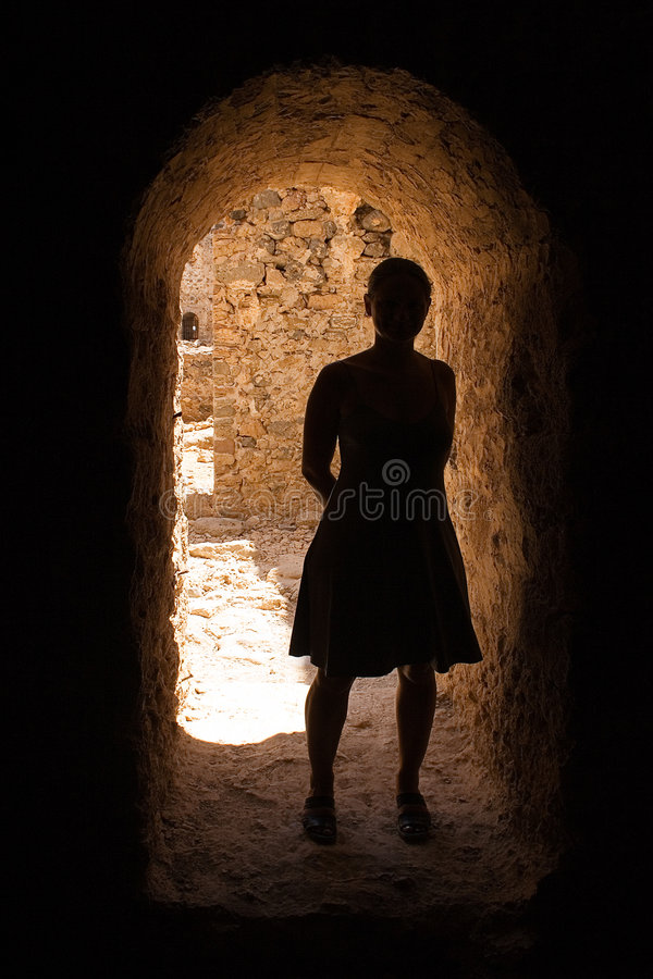 Silhouette Under Arch. Silhouette of a female in the shadows of an ancient building stock images