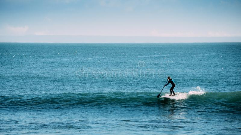 Silhouette of unidentifiable man castching a wave while on a stand up paddle board stock photography