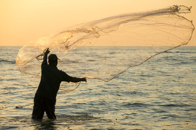 Silhouette of the unidentified Indian fisherman throwing net in sea royalty free stock image