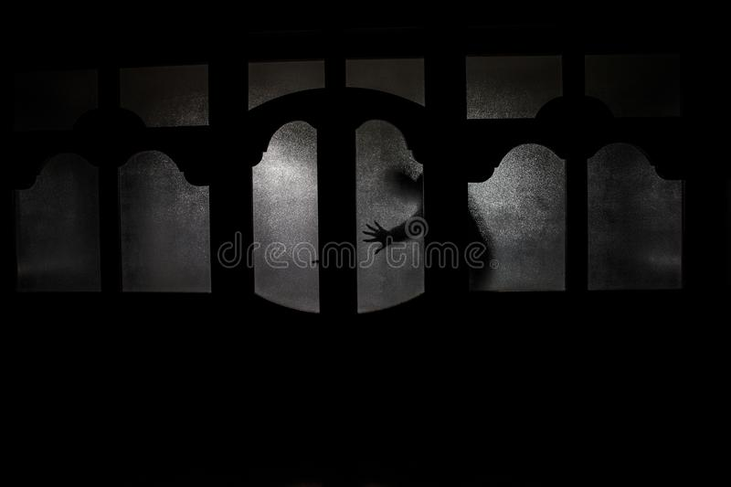 Silhouette of an unknown shadow figure on a door through a close stock images