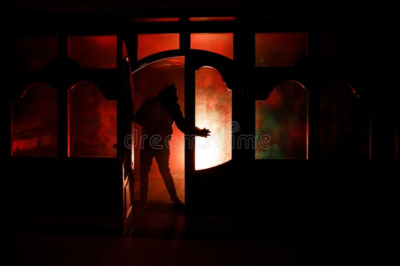 Silhouette of an unknown shadow figure on a door through a closed glass door. The silhouette of a human in front of a window at ni vector illustration