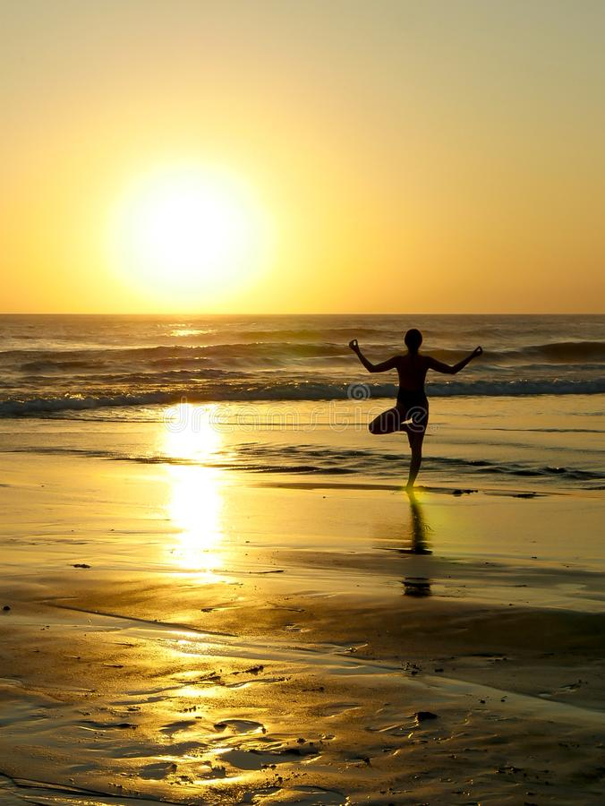 Silhouette of unknown unrecognizable woman standing on beach sea water practicing yoga and meditation looking to the sun on the ho stock images