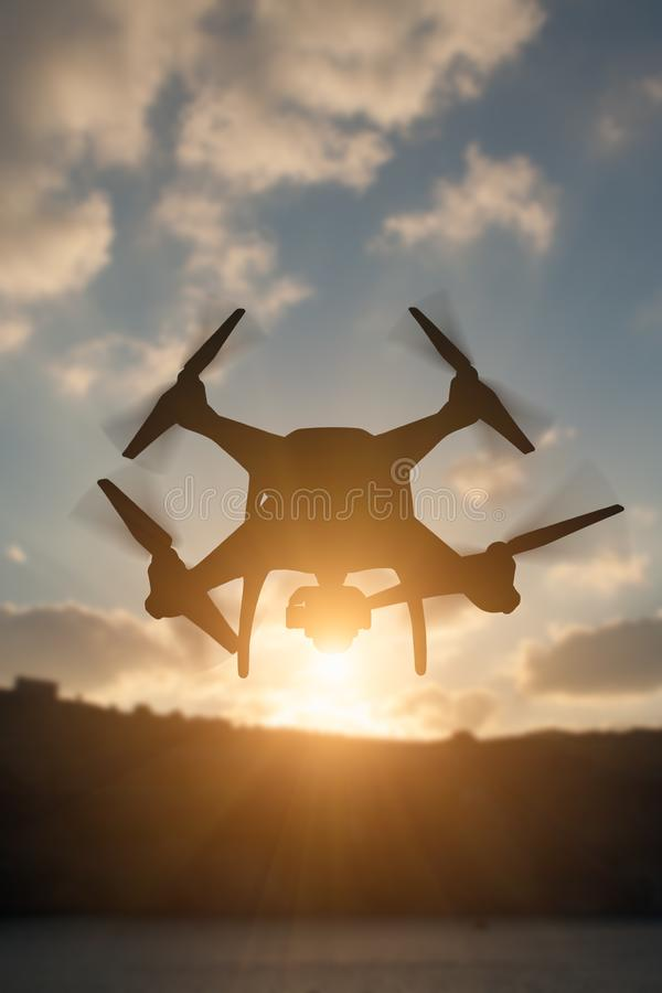 Silhouette of Unmanned Aircraft System UAV Quadcopter Drone In royalty free stock photography