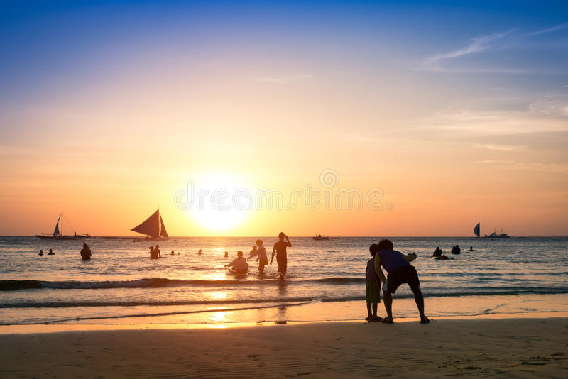 Silhouette of unrecognizable tourists and local people with father and son taking selfie at Boracay beach during sunset - stock images