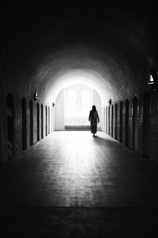 Silhouette of unrecognizable woman in medieval room. Silhouette of unrecognizable sleepwalking woman in medieval mental hospital stock photo