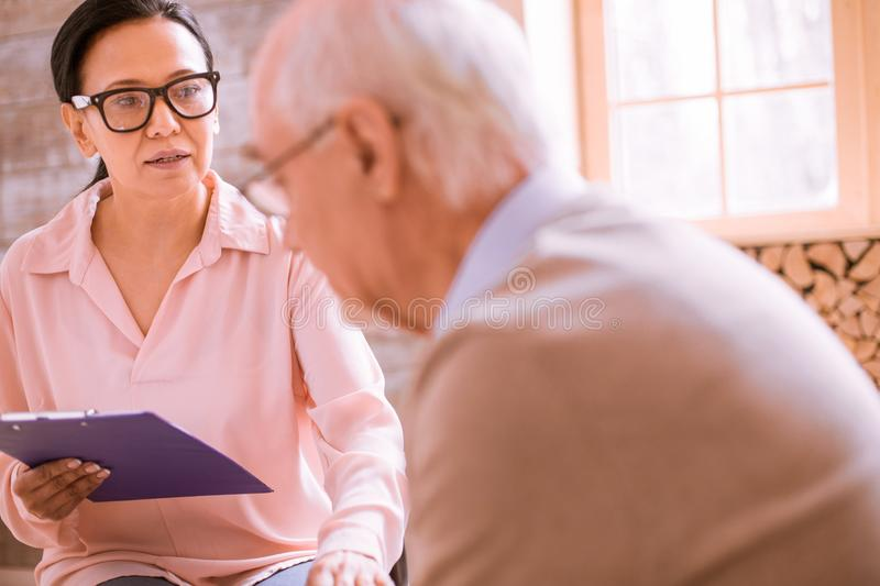 Silhouette of upset retirement that talking to psychologist. Family problem. Kind female person holding folder in right hand, supporting her upset patient royalty free stock image
