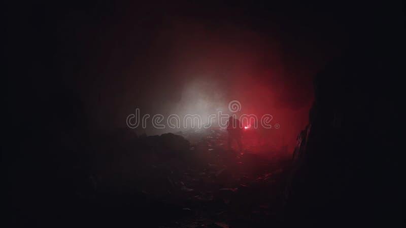 Silhouette van een geoloog die de donkere grot onderzoekt, die de rode signaalfslag vasthoudt Beeldmateriaal Wetenschappers die s royalty-vrije stock fotografie