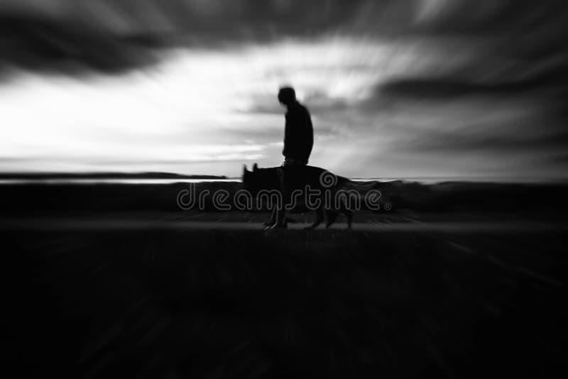 Silhouette in verschwommener Bewegung des Menschen, der seinen Hund in Schwarz-Weiß führt lizenzfreie stockfotos