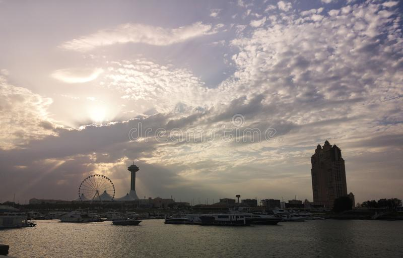 Silhouette view of Abu Dhabi city Marina Mall, Marina eye wheel and Fairmont Marina Residences against clouds at sunset.  royalty free stock photo