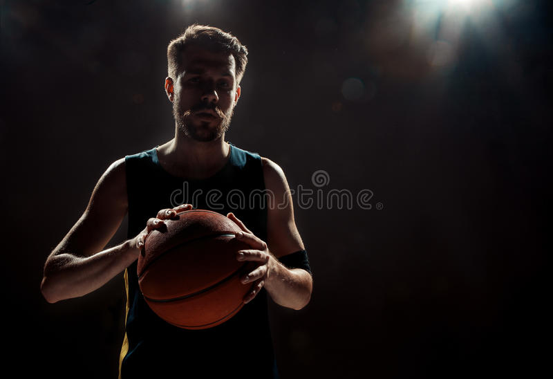 Silhouette view of a basketball player holding basket ball on black background stock photos