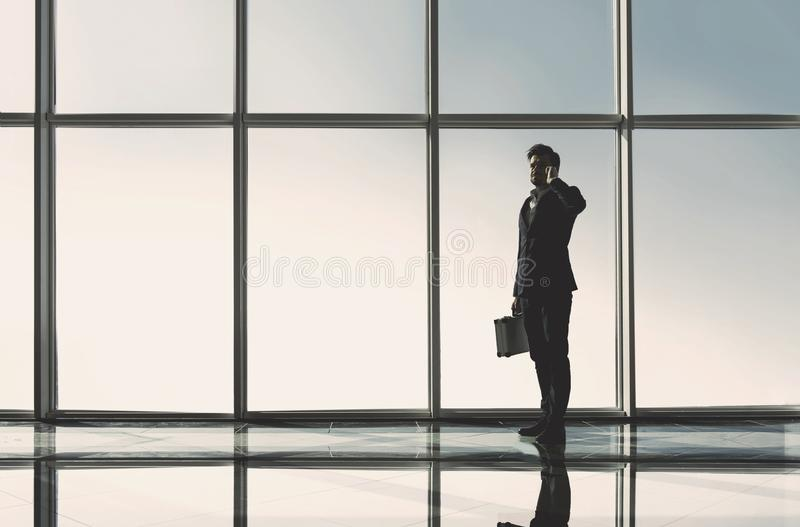 Silhouette view of young businessman is standing in modern office with panoramic windows.  royalty free stock image