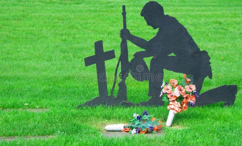 Silhouette von Soldier Kneeling auf dem Friedhof der Veteranen lizenzfreie stockbilder