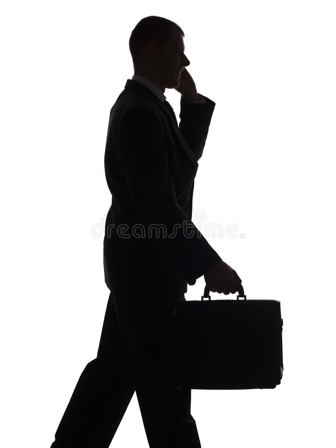 Silhouette of walking man with suitcase and cell stock image