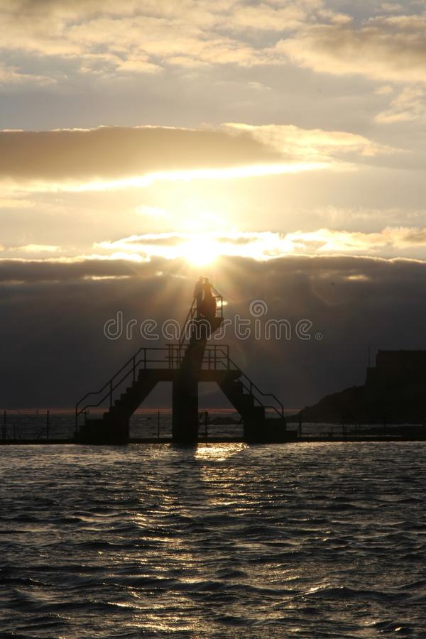 Silhouette of wedding couple on top of a diving board at sunset. St Malo in France royalty free stock photos
