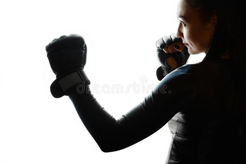 Silhouette of a white sports woman in a protective gesture in profile against a white background. Portrait. Copy space. Concept of. Self-defence, protection royalty free stock image