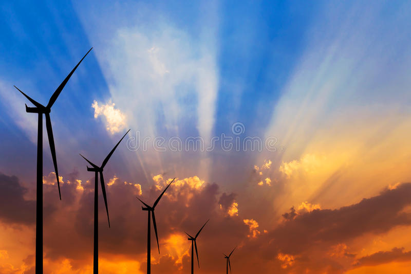Silhouette wind turbines generating electricity. On sunset background royalty free stock image