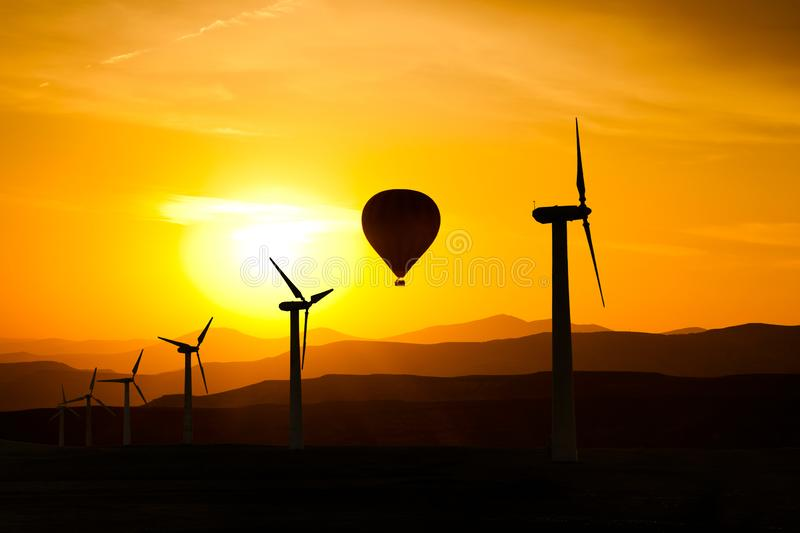 Silhouette of wind turbines and a hot air balloon at sunset stock images