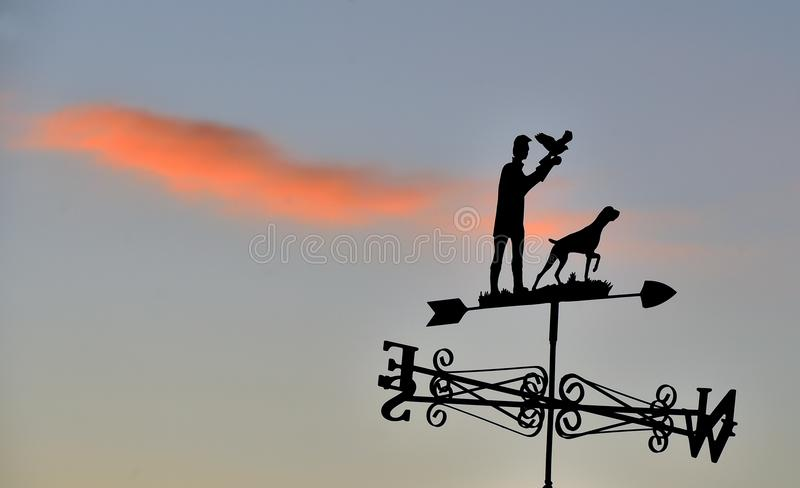 Silhouette wind vane of man with bird of prey and gun dog in Wiltshire royalty free stock photography