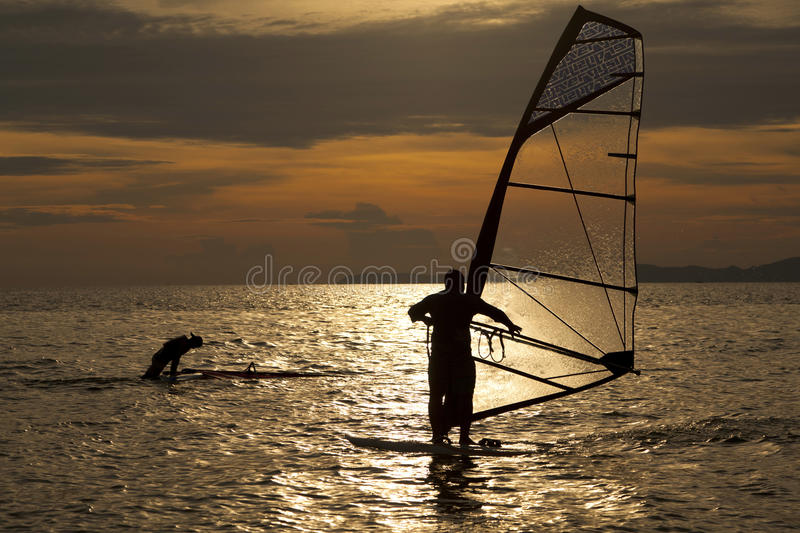 Silhouette of windsurfers. In the sunset sea stock photo