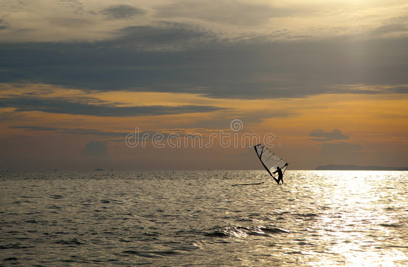 Silhouette of windsurfers. In the sunset sea royalty free stock photography