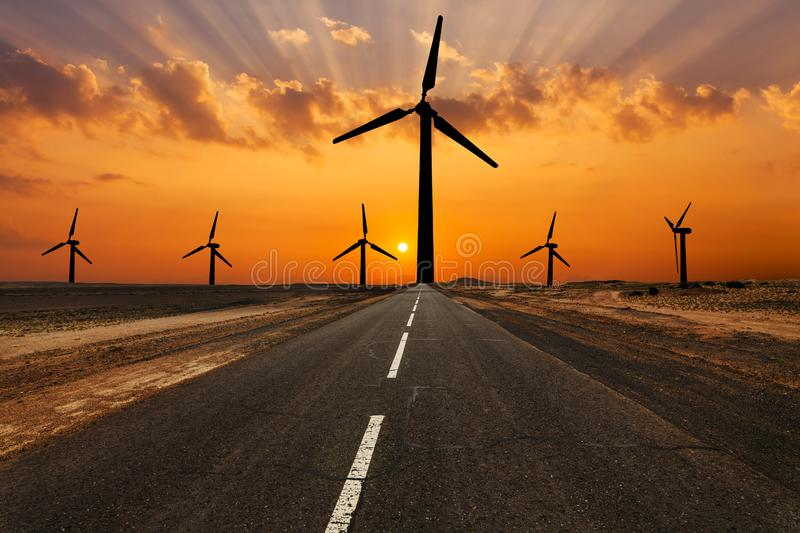 Silhouette of windturbines on an amazing sunset. Road and windturbines on an amazing sunset royalty free stock photography