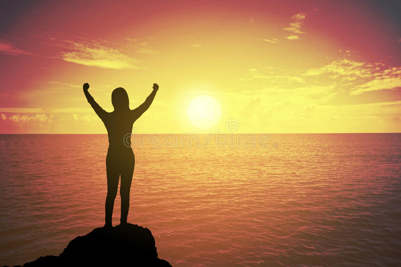 Silhouette of winning success woman at sunset or sunrise standing and raising up hand in celebration of having reached mountain. stock photo
