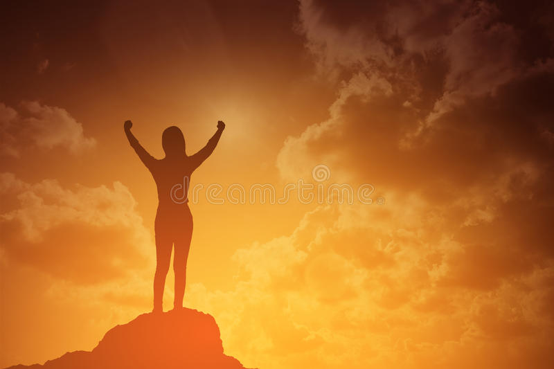 Silhouette of winning success woman at sunset or sunrise standing and raising up her hand in celebration.business success concept stock images