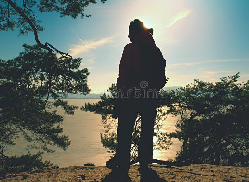 Silhouette of winter clothed woman walking at icy lake in sunset. Weather water traveler tourist top sunrise sunny day sunlight sunglasses snow sky single royalty free stock images