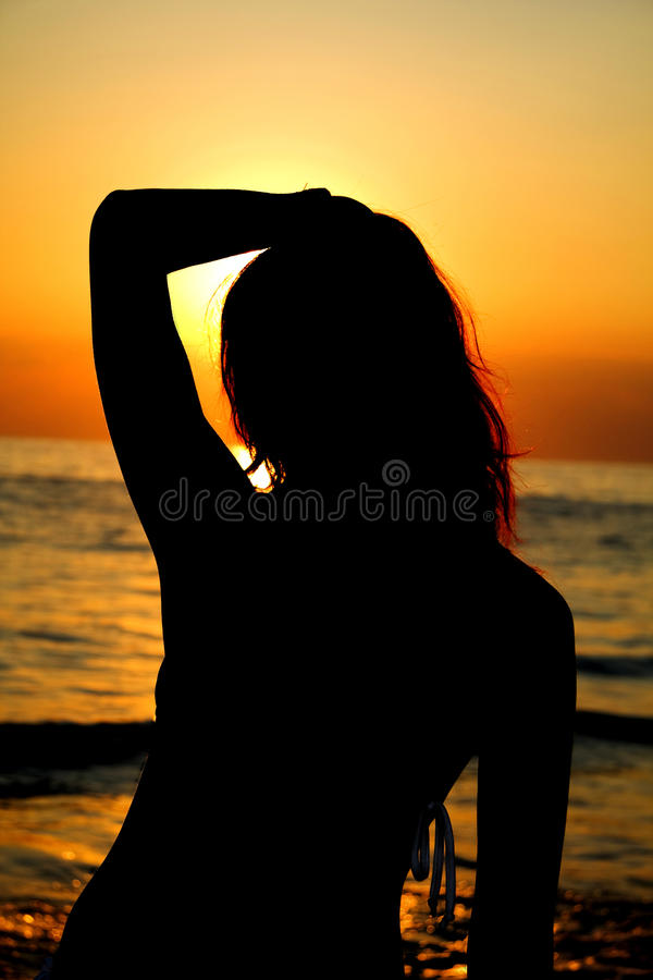 Silhouette of a woman against the ocean at sunset. Summer evening royalty free stock photography