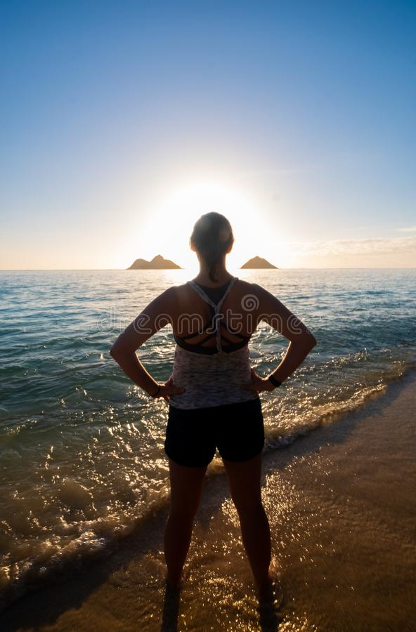 Silhouette of woman against sun rising between islands. A sunrise in the distance between two islands off Oahu, Hawaii, USA. A woman faces them, looking out over stock images