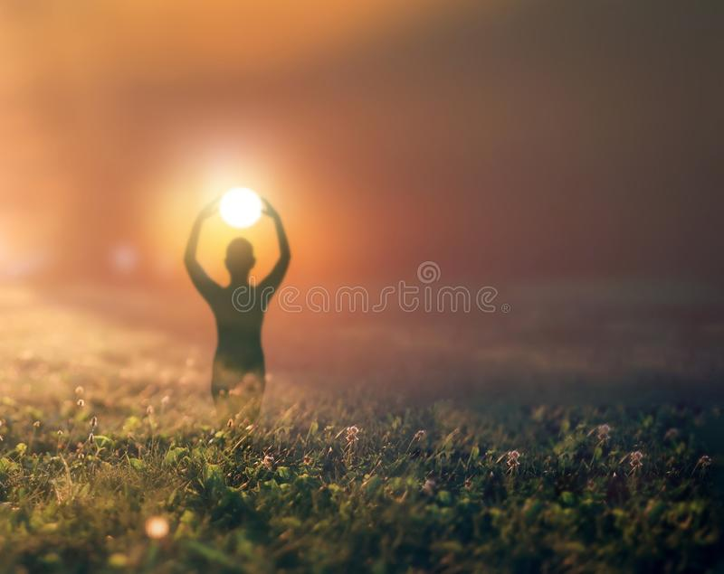 Silhouette of a woman against the sunset. Happy young woman enjoying summer vacation and holds both hands over the head so as like she holds the sun on the royalty free stock photo