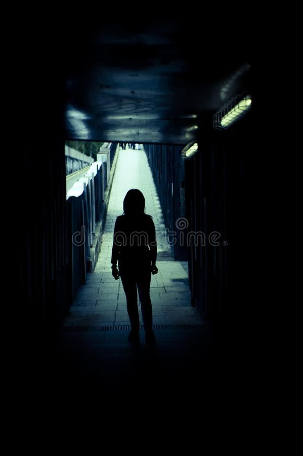 Silhouette of woman alone at the end of a tunnel. Woman alone and sad in a tunnel. Scene of mystery and desolation stock photos