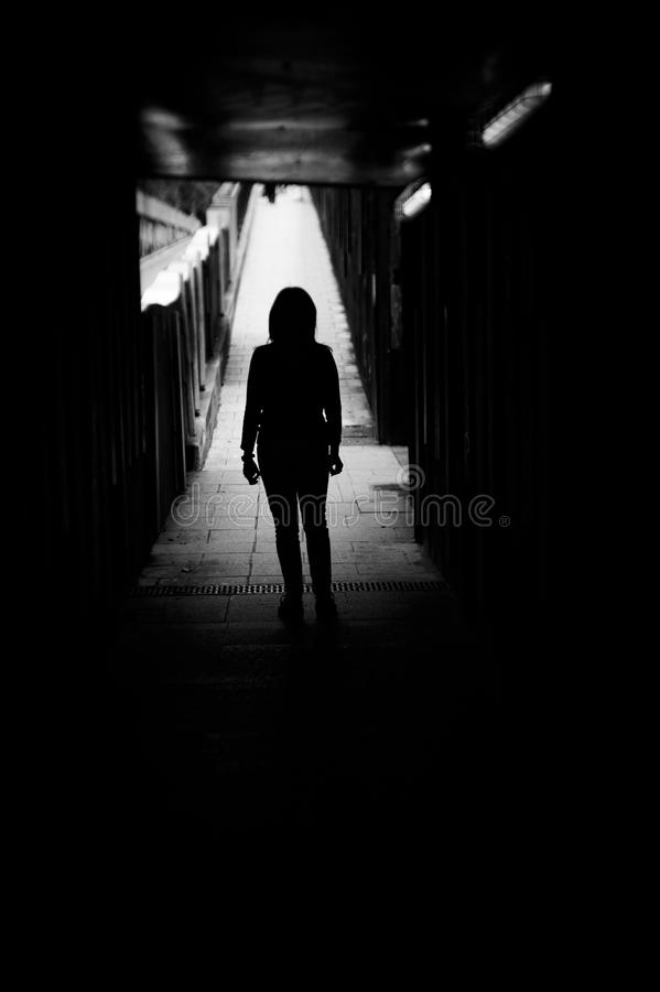 Silhouette of woman alone at the end of a tunnel. Woman alone and sad in a tunnel. Scene of mystery and desolation royalty free stock photo