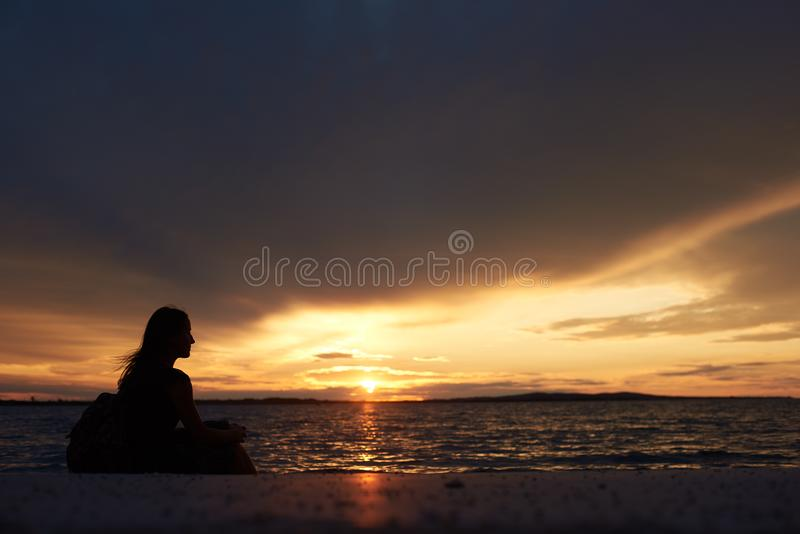 Silhouette of woman alone at water edge, enjoying beautiful seascape at sunset. royalty free stock photos