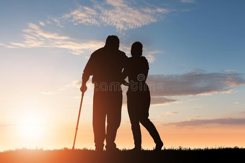 Silhouette Of Woman Assisting Her Disabled Father royalty free stock images