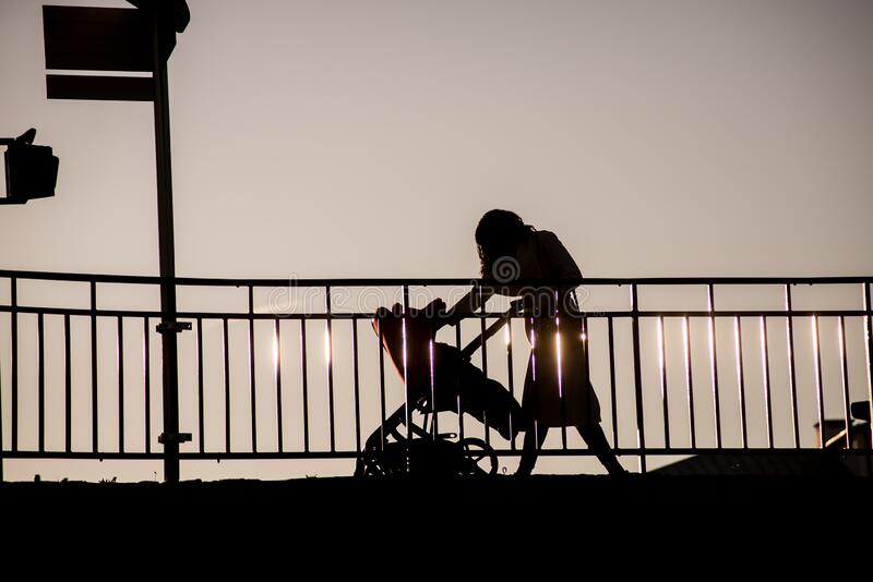 Woman with baby in a trolley walking on bridge under the river by sunset. Silhouette of woman with baby in a trolley walking on bridge under the river by sunset royalty free stock photography
