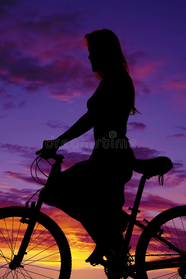 Silhouette of a woman on a bike up close stock image