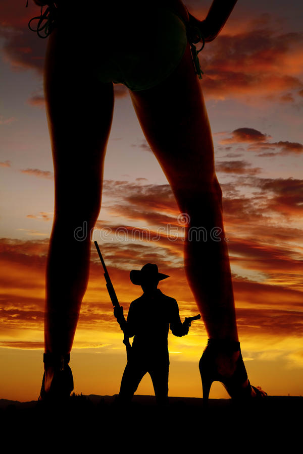 Silhouette woman in bikini heels legs one turned to side cowboy. A silhouette of a woman in her bikini with her cowboy holding weapons in the middle of her legs stock photography