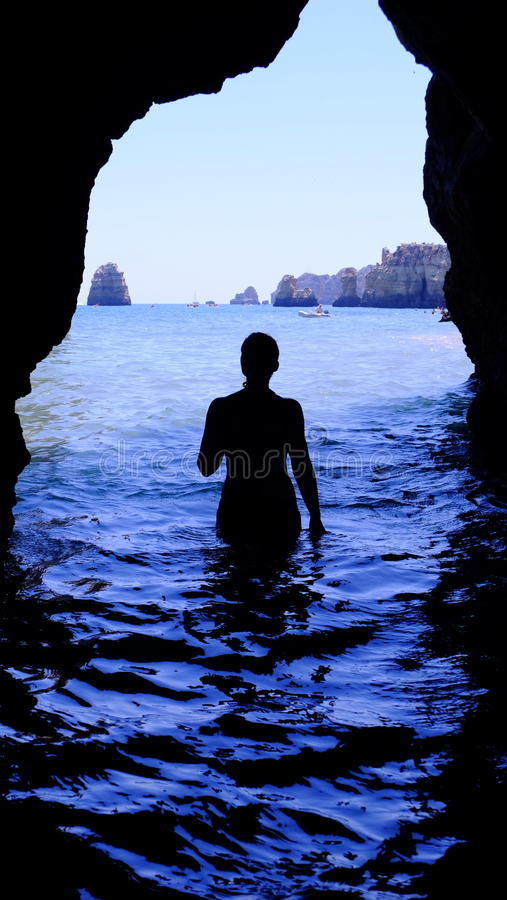Silhouette of Woman at Blue Sea Inside Black Cave during Daytime stock images