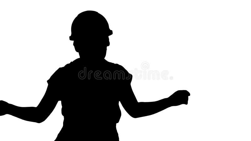 Silhouette Woman in construction helmet dancing. stock photo