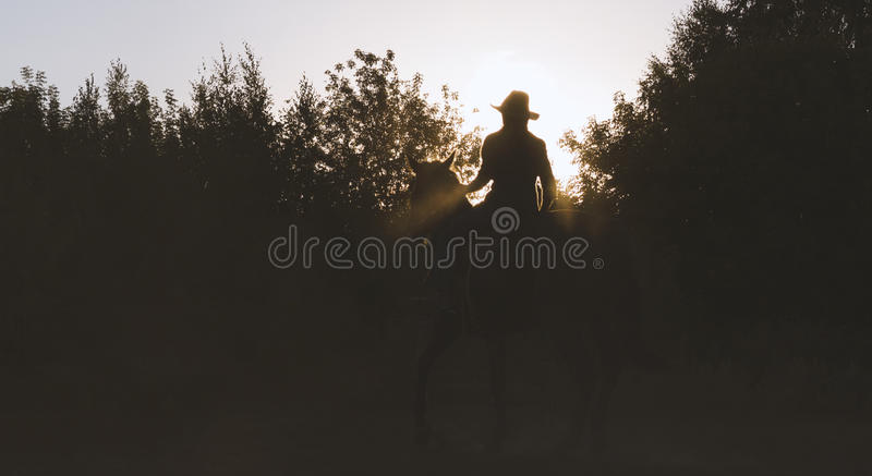 Silhouette of a woman in cowboy hat riding a horse - sunset. View royalty free stock image