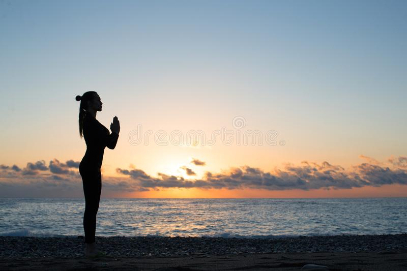 Silhouette of woman doing greeting to the sun on the beach at sunrise, morning yoga royalty free stock photo